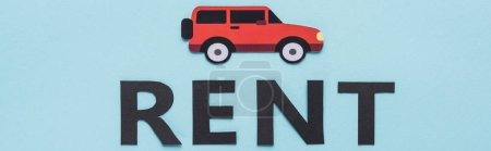 top view of paper cut car and black rent lettering on blue background, panoramic shot