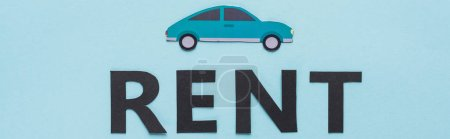 Photo for Top view of paper cut car and black rent lettering on blue background, panoramic shot - Royalty Free Image