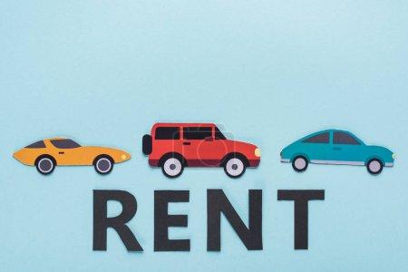vista superior de papel cortar varios coches y alquiler de letras sobre fondo azul
