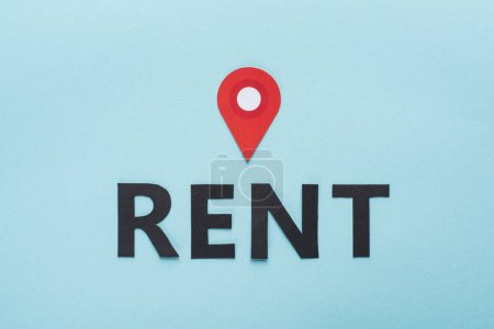top view of paper cut black rent lettering and red location mark on blue background