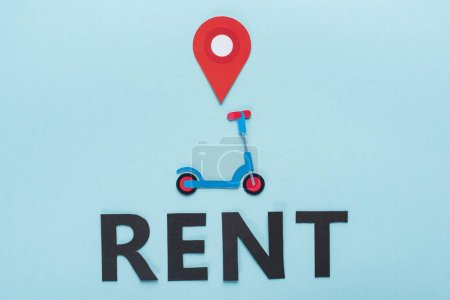 top view of paper cut kick scooter with location mark near black rent lettering on blue background
