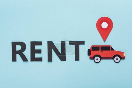 top view of paper cut car with location mark near black rent lettering on blue background