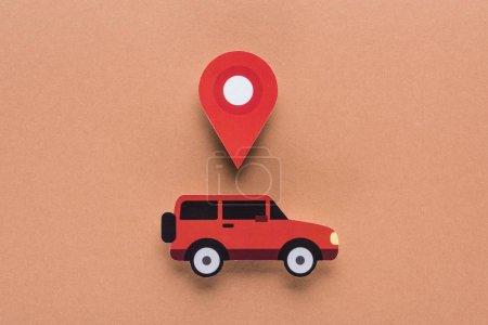 Photo pour Vue du haut de la voiture de papier coupé et marque de localisation sur fond brun, concept de location de voiture - image libre de droit