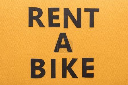 Photo pour Vue du dessus du papier coupé noir louer un lettrage de vélo sur fond orange - image libre de droit