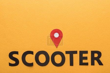 Photo pour Vue du dessus du papier coupé lettrage scooter noir et marque de localisation rouge sur fond orange - image libre de droit