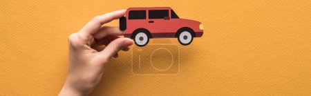 cropped view of woman holding paper cut car on orange background, panoramic shot