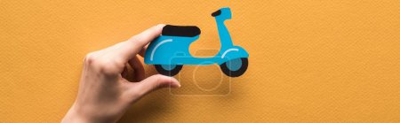 cropped view of woman holding paper cut scooter on orange background, panoramic shot
