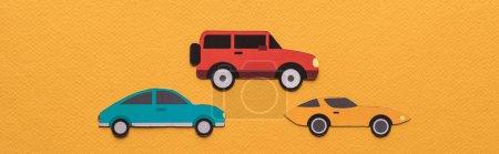 Foto de Vista superior de los coches cortados en papel y letras negras de alquiler en fondo naranja, disparo panorámico. - Imagen libre de derechos