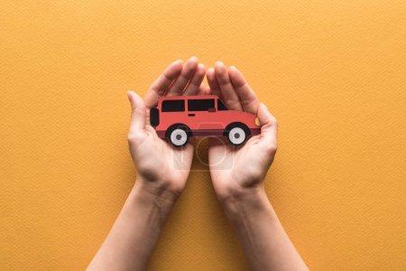 Photo pour Vue partielle de la femme tenant le papier coupé voiture sur fond orange - image libre de droit