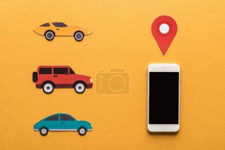 Draufsicht auf Papier geschnittene Autos, Ortsmarke in Smartphone-Nähe mit leerem Bildschirm auf orangefarbenem Hintergrund