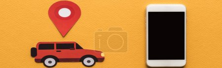 Photo for Top view of paper cut car, location mark near smartphone with blank screen on orange background, panoramic shot - Royalty Free Image