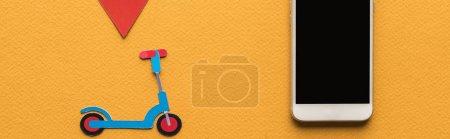 Foto de Visión superior del tirador de papel cortado, marca de ubicación cerca de smartphone con pantalla en blanco sobre fondo naranja, disparo panorámico. - Imagen libre de derechos