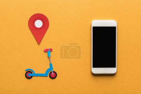 top view of paper cut kick scooter, location mark near smartphone with blank screen on orange background