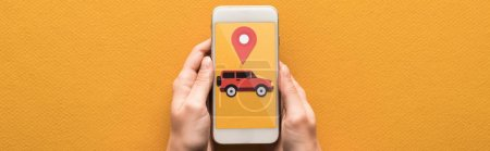 cropped view of woman holding smartphone with rent car app on orange background, panoramic shot