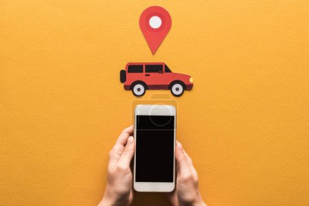 cropped view of woman holding smartphone with blank screen near paper cut car, location mark on orange background