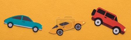 Photo pour Vue du dessus des voitures coupées en papier sur fond orange, panoramique - image libre de droit