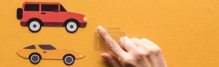 Photo pour Vue recadrée d'une femme pointant du doigt des voitures en papier sur fond orange, prise de vue panoramique - image libre de droit