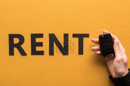 Photo pour Vue en coupe d'une femme tenant la clé d'une voiture près d'une feuille de papier location lettrage sur fond orange - image libre de droit