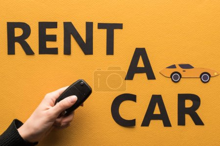 Photo pour Vue recadrée de femme tenant clé près de papier coupé louer une voiture lettrage sur fond orange - image libre de droit