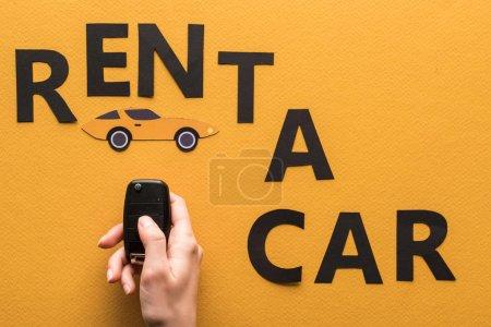 Photo pour Vue en coupe d'une femme tenant une clé près d'un papier coupé location d'une voiture lettrage sur fond orange - image libre de droit