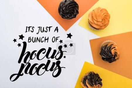Photo pour Vue du haut de délicieux cupcakes d'Halloween sur fond jaune, orange et blanc avec elle est juste un tas d'illustration de pocus hocus - image libre de droit