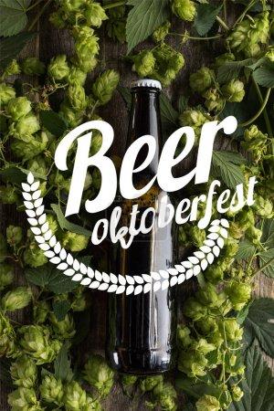 Photo pour Vue du dessus de la bière fraîche en bouteille avec houblon vert sur la surface en bois avec bière Oktoberfest illustration - image libre de droit