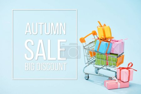Photo for Festive wrapped presents in shopping cart on blue background with autumn sale big discount illustration - Royalty Free Image