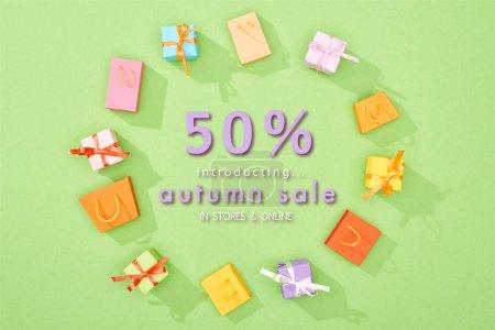 Photo pour Cadre rond de boîtes-cadeaux décoratives et de sacs à provisions sur fond vert avec illustration de 50 p. - image libre de droit