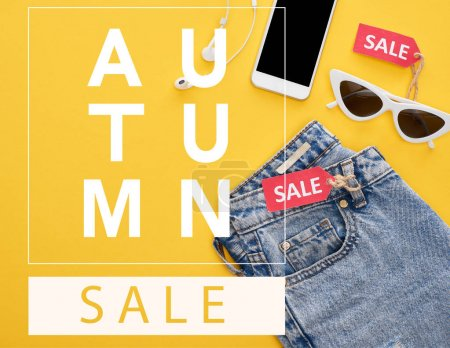 Photo for Top view of jeans, glasses and smartphone with earphones with sale labels on yellow background with autumn sale illustration - Royalty Free Image
