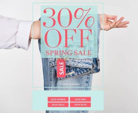 Photo pour Vue en coupe d'une femme tenant des jeans suspendus avec étiquette de vente isolée sur blanc avec vente au printemps 30 pour cent de réduction - image libre de droit