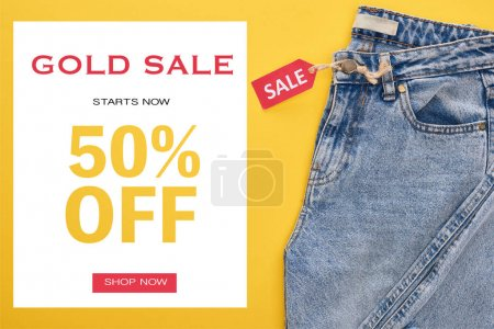 Photo pour Top view of jeans with sale label on yellow background with gold sale 50 % off illustration - image libre de droit