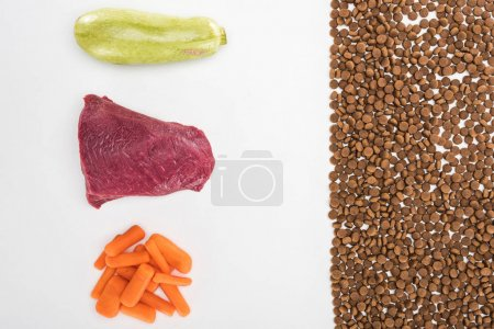 flat lay with dry pet food near raw meat, carrot and zucchini isolated on white
