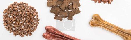 Foto de Vista superior de una variedad de alimentos secos para mascotas y huesos aislados en blanco, plano panorámico - Imagen libre de derechos