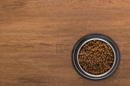 top view of dry pet food in silver bowl on wooden table