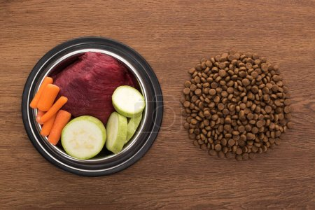 Photo for Top view of dry pet food near raw vegetables and meat in bowl on wooden table - Royalty Free Image
