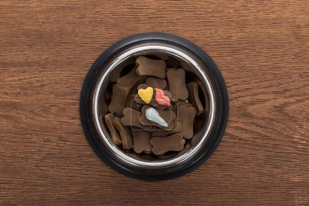 top view of dry pet food in silver bowl with vitamins on wooden table
