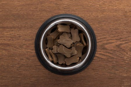Photo for Top view of dry pet food in silver bowl on wooden table - Royalty Free Image