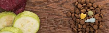 top view of raw meet, zucchini near vitamins on dry pet food on wooden table, panoramic shot