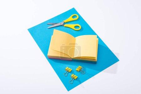 Photo pour Vue à angle élevé d'un bloc-notes, de ciseaux, de pinces de reliure et de papier sur fond blanc - image libre de droit