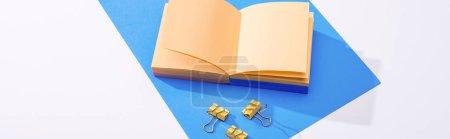 Photo pour Photographie panoramique d'un cahier, de pinces à reliure et de papier sur fond blanc - image libre de droit