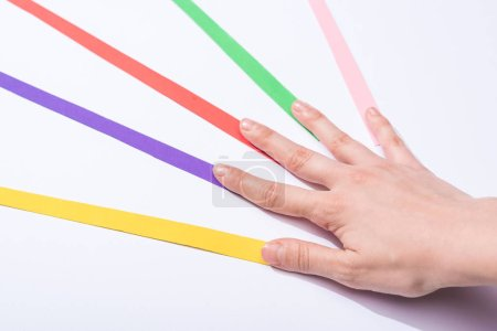 Photo pour Vue recadrée de la femme touchant bandes de papier coloré sur fond blanc - image libre de droit