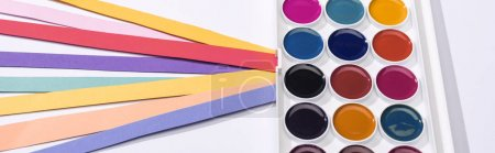 panoramic shot of watercolor and bright paper strips on white background