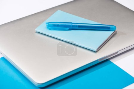 Foto de Vista de gran angular de cuaderno colorido, bolígrafo azul, portátil, papel sobre fondo blanco. - Imagen libre de derechos