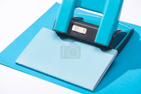 Photo for High angle view of notebook, holepunch and paper isolated on white - Royalty Free Image