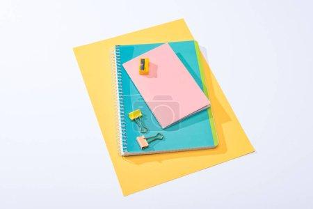 Foto de Vista de gran angular de cuadernos, clips de encuadernado, nitidez y papel sobre fondo blanco. - Imagen libre de derechos