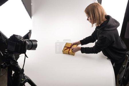 Photo pour Beau photographe prenant des photos de Noël cadeau sur appareil photo numérique sur blanc en studio photo - image libre de droit