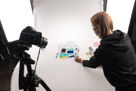 Photo for Professional photographer making flat lay with office supplies for commercial photo shooting on white - Royalty Free Image