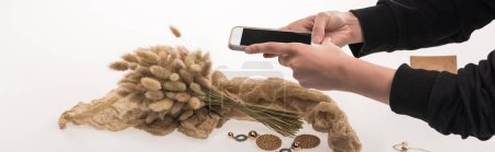 Photo for Partial view of commercial photographer taking pictures of composition with flora and jewelry on smartphone on white, panoramic shot - Royalty Free Image