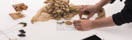 Photo for Partial view of commercial photographer making composition with flora and jewelry for commercial photography on smartphone on white, panoramic shot - Royalty Free Image
