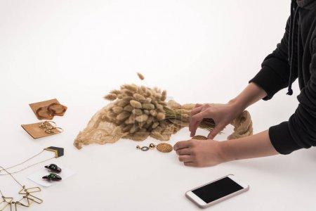 Photo pour Vue partielle du photographe commercial faisant composition avec flore et bijoux pour la photographie commerciale sur smartphone sur blanc - image libre de droit